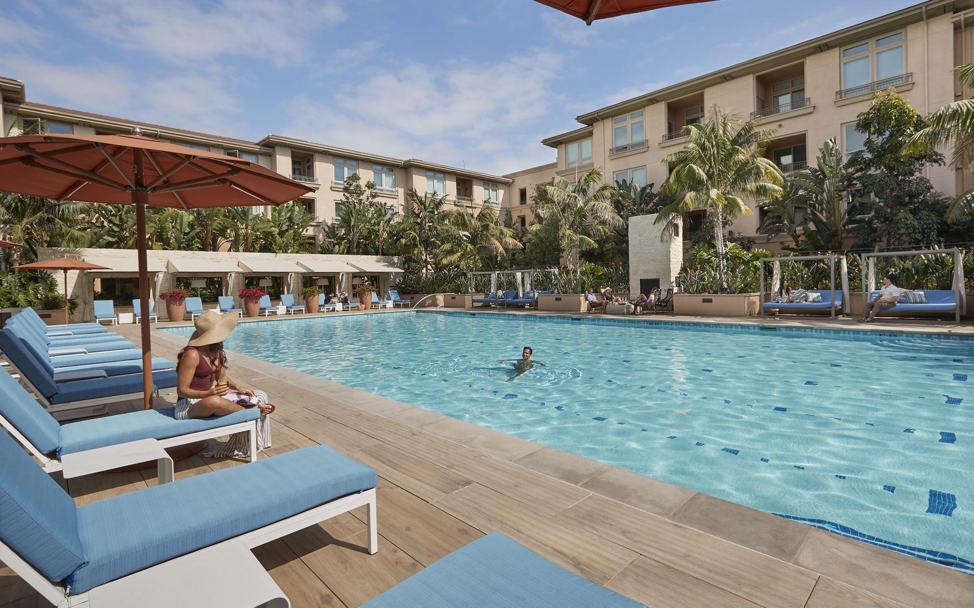 Exterior view of people spending time by pool at Villas at Playa Vista Apartment Homes in Playa Vista, CA.