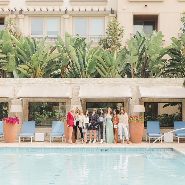 View of a group of women outside by the pool at Montecito at Villas Playa Vista Apartment Homes in Los Angeles, CA.