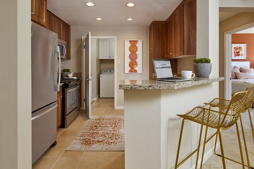 Interior view of kitchen and laundry room at Cherry Orchard Apartment Homes in Sunnyvale, CA.