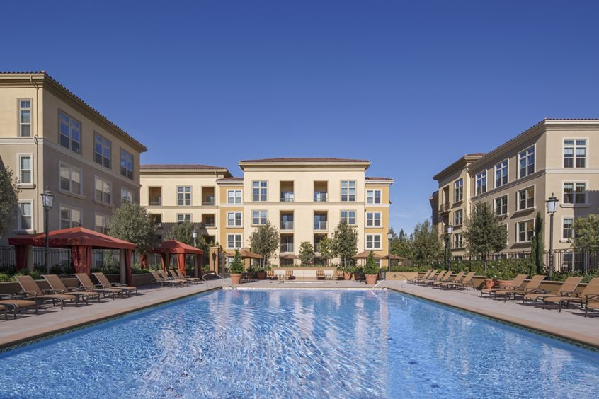 View of building exterior and pool at Crescent Village Apartment Homes in San Jose, CA.
