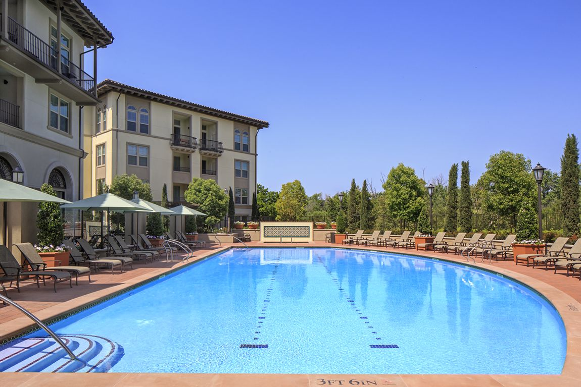 View of building exterior and pool at Verona at Crescent Village Apartment Homes in San Jose, CA.