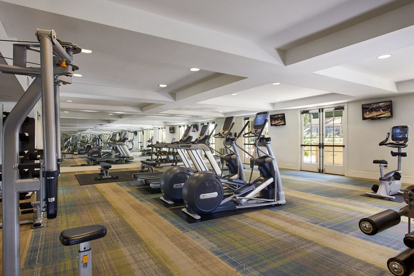 Interior view of fitness center at The Cypress at North Park Apartment Homes in San Jose, CA.