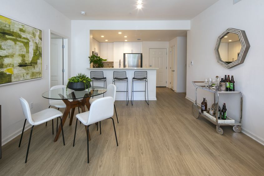 Interior view of a dining space and kitchen at The Oaks at North Park Apartment Homes in San Jose, CA.