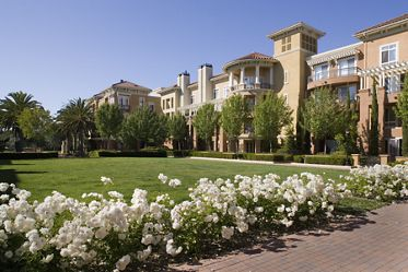 View of building exterior and courtyard at The Pines at North Park Apartment Homes in San Jose, CA.