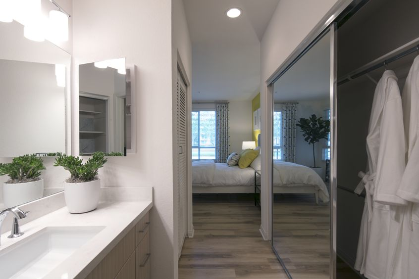 Interior view of a bathroom and closet at The Pines at North Park Apartment Homes in San Jose, CA.