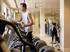 Interior view of a couple at the fitness center at The Sycamores at North Park Apartment Homes in San Jose, CA.
