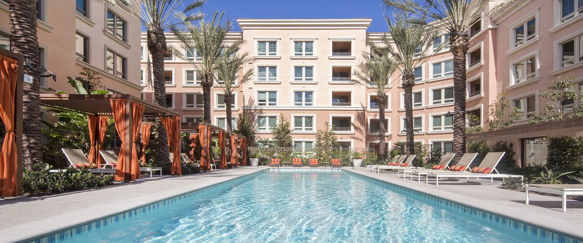 View of building exterior and pool at Santa Clara Square Apartment Homes in Santa Clara, CA.