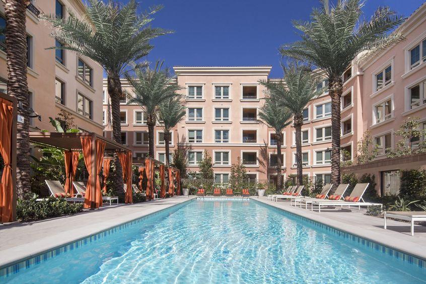 View of building exterior and pool at Santa Clara Square Apartment Homes in Santa Clara, CA.