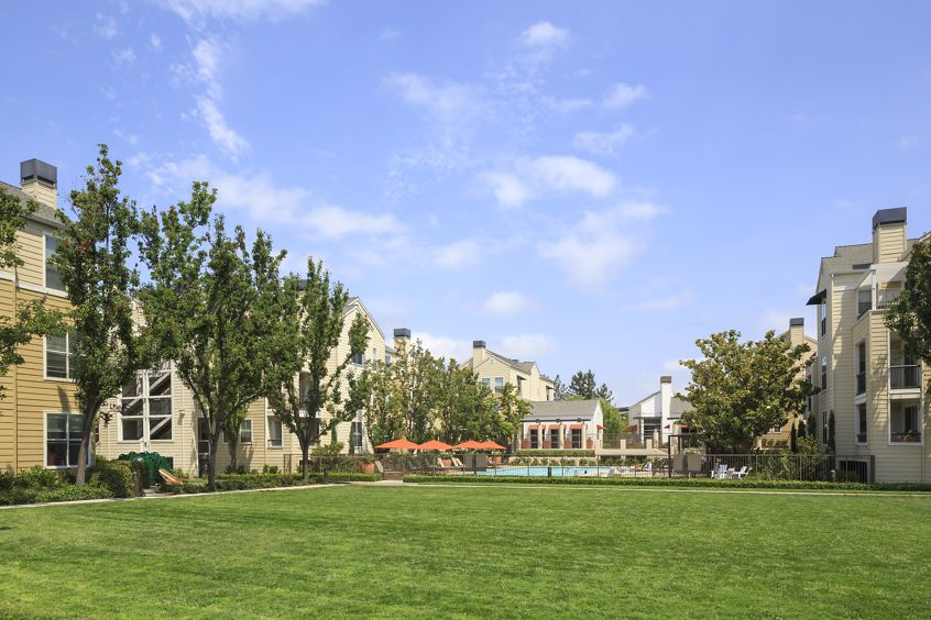 View of building exterior and lawn area at The Hamptons Apartment Homes in Cupertino, CA.