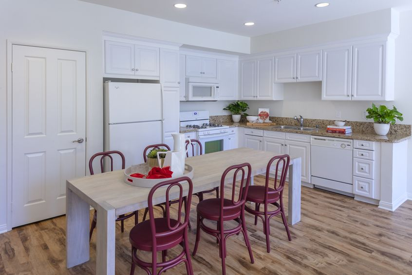 Interior view of dining room and kitchen at Murano Apartment Homes at Cypress Village in Irvine, CA.