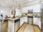 Interior view of kitchen and dining room at Los Olivos Apartment Homes at Irvine Spectrum in Irvine, CA.