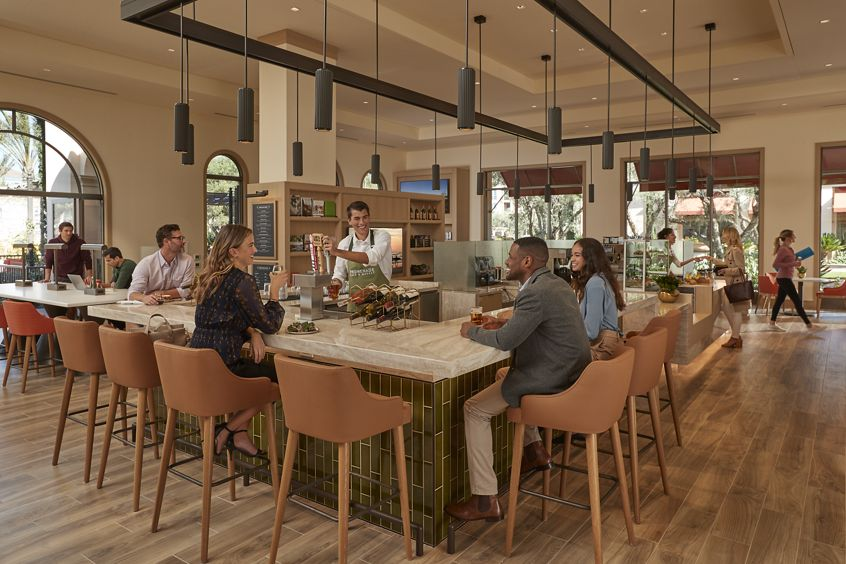 Interior view of people dining at Cafe & Market at Promenade Apartment Homes in Irvine, CA.