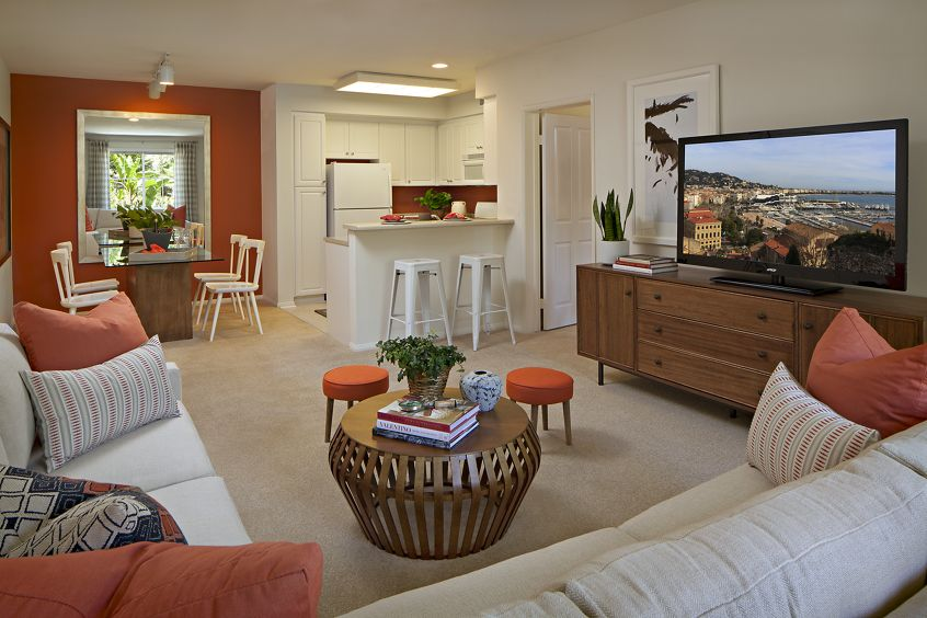 Interior view of living room, dining room, and kitchen at Serrano Apartment Homes in Irvine, CA.