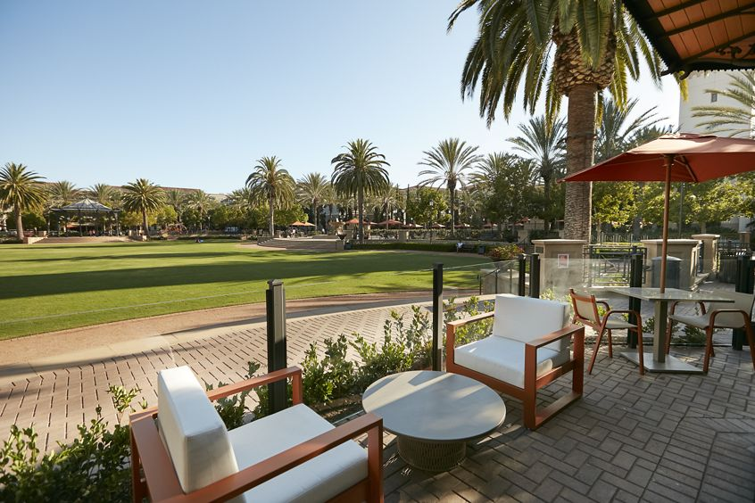 Exterior view of outdoor seating near courtyard at The Park at Irvine Spectrum Apartment Homes in Irvine, CA.