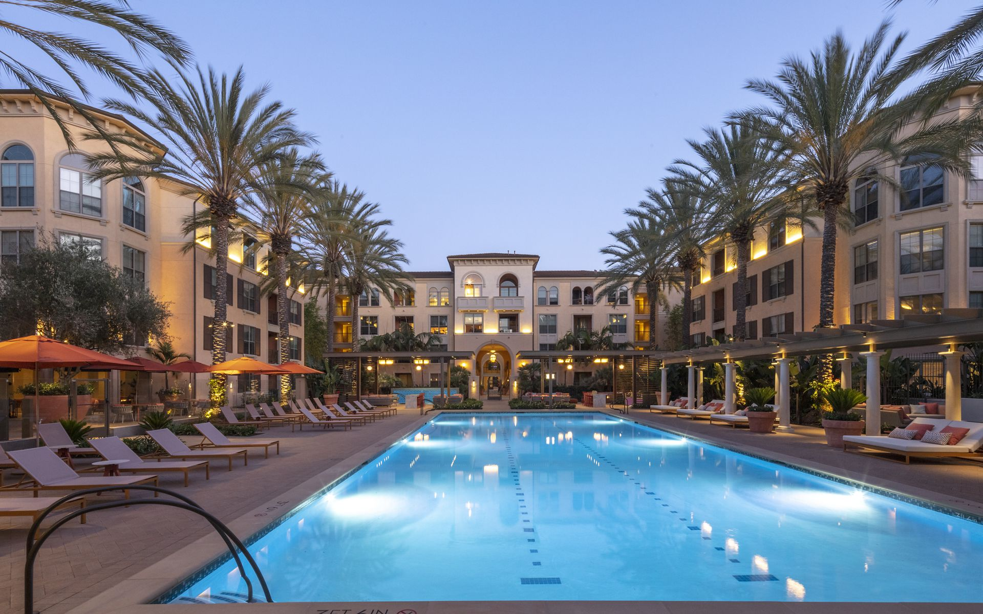 Exterior evening pool view at Delrey at The Village at Irvine Spectrum Apartment Homes in Irvine, CA.