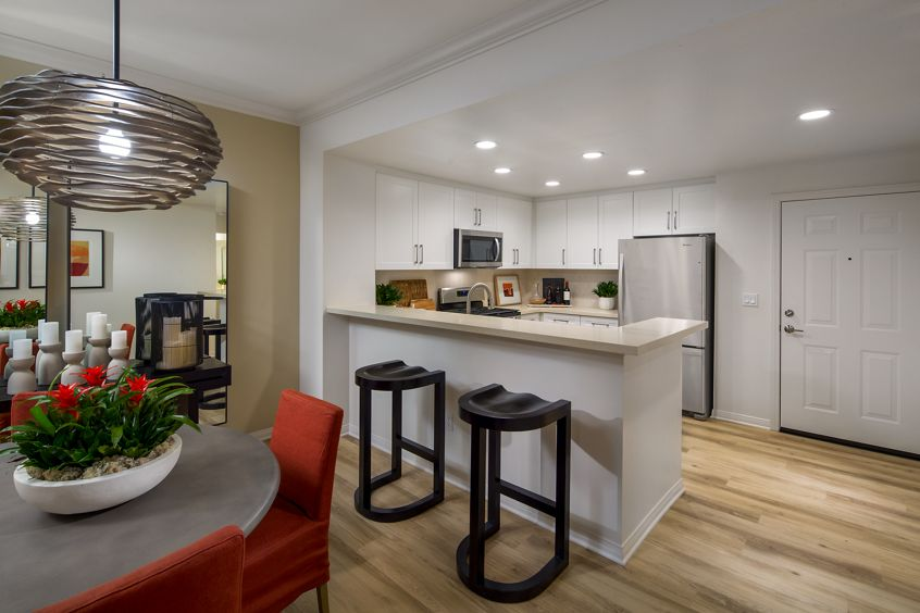 Interior view of kitchen and dining room at Mirador at The Village at Irvine Spectrum Apartment Homes in Irvine, CA.