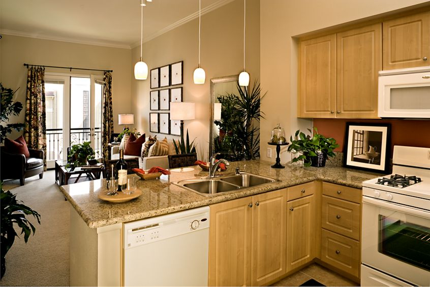 Interior views of  kitchen and living area at The Village Serena at Irvine Spectrum Apartment Homes in Irvine, CA.
