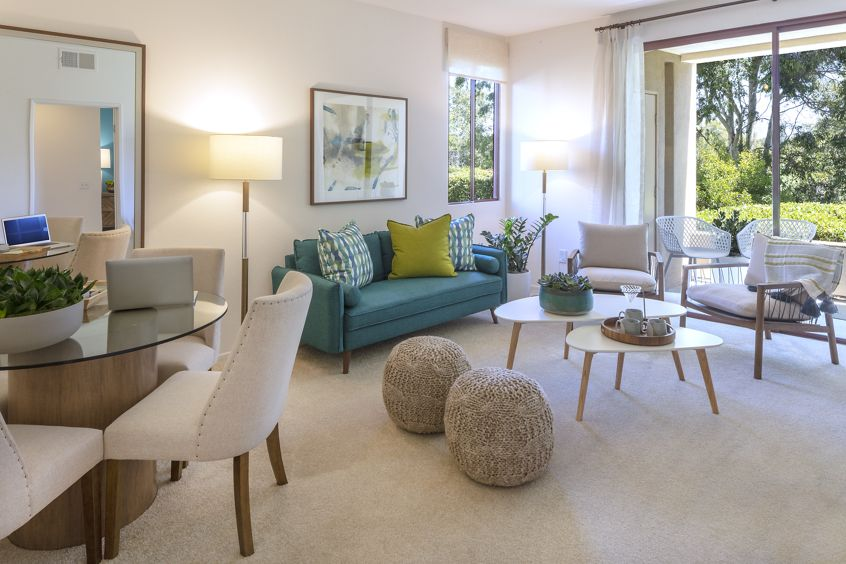 Interior view of living room and dining room at Ambrose Apartment Homes at University Town Center in Irvine, CA.