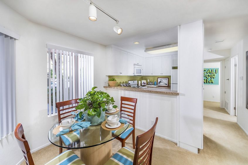 Interior view of kitchen and dining room at Berkeley Court Apartment Homes at University Town Center in Irvine, CA.