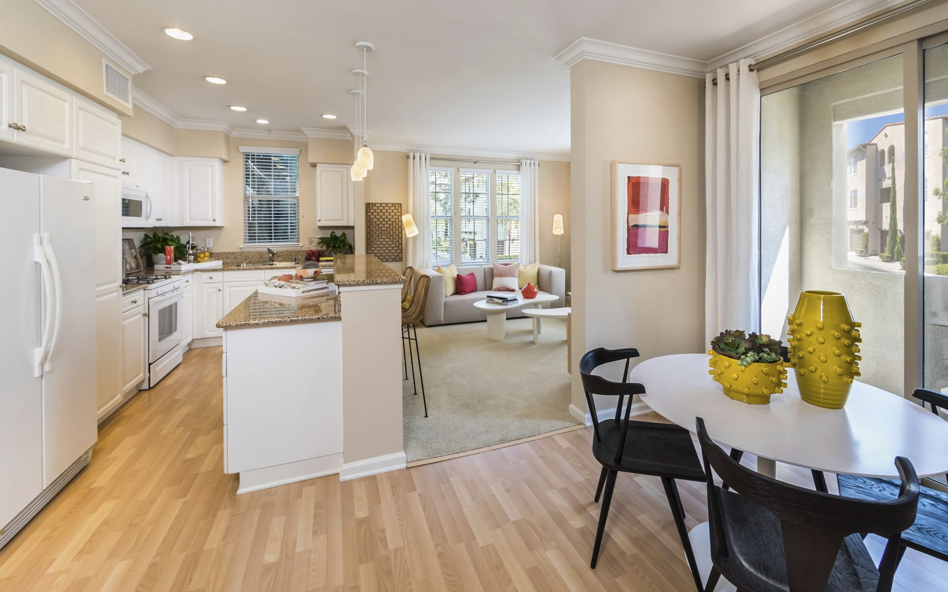 Interior view of dining room and kitchen at Woodbury Lane Apartment Homes in Irvine, CA.