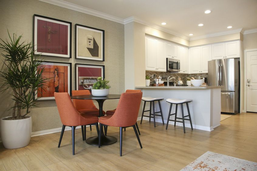Interior view of dining room and kitchen at Bordeaux Apartment Homes in Newport Beach, CA.