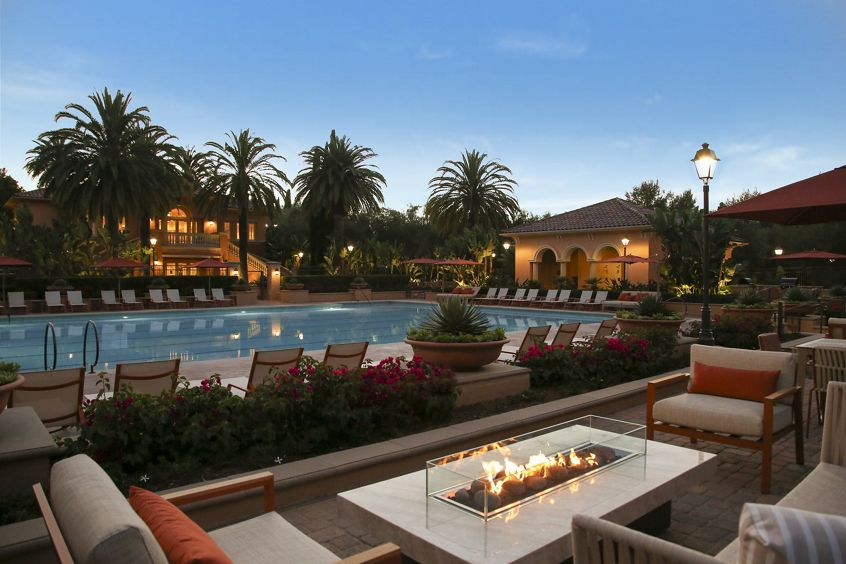 Exterior evening view of pool at Newport Bluffs Apartment Homes in Newport Beach, CA.