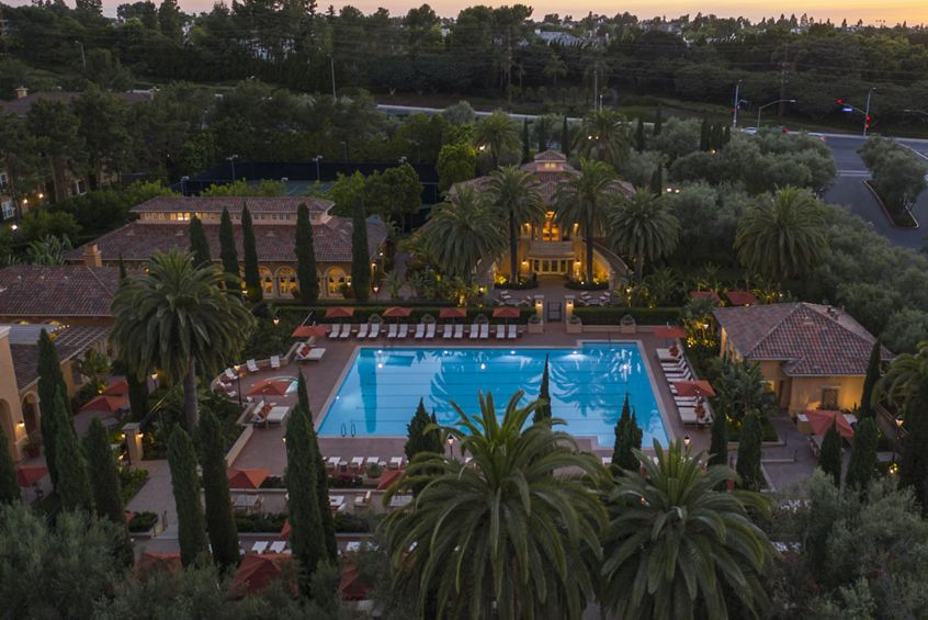 Exterior evening aerial view of pool at Newport Bluffs Apartment Homes in Newport Beach, CA.