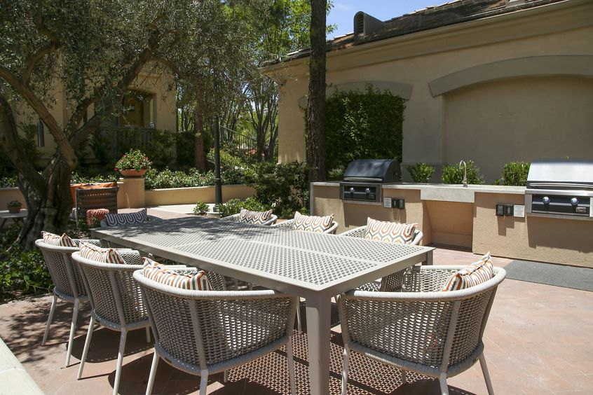 Exterior view of courtyard with outdoor seating and BBQ at Newport Ridge Apartment Homes in Newport Beach, CA.