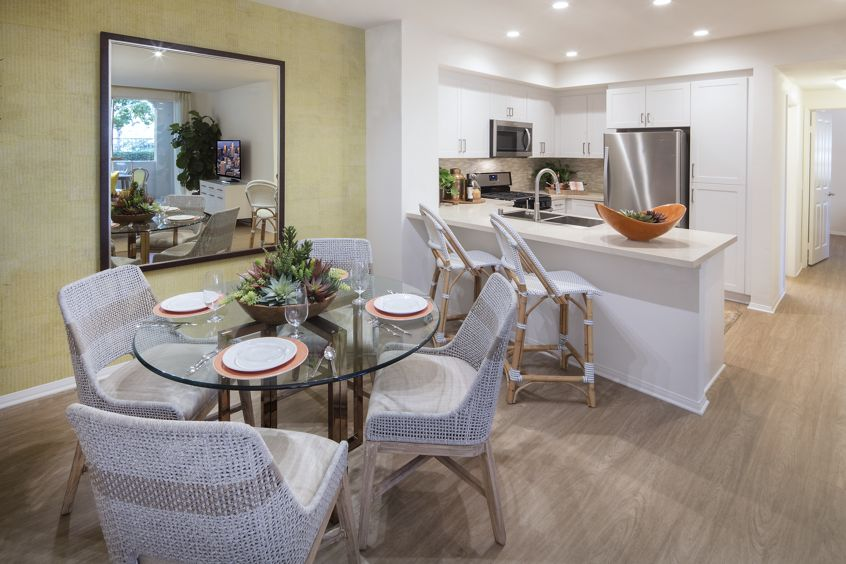 Interior view of a dining space and kitchen at Turtle Ridge Apartment Homes in Newport Beach, CA.