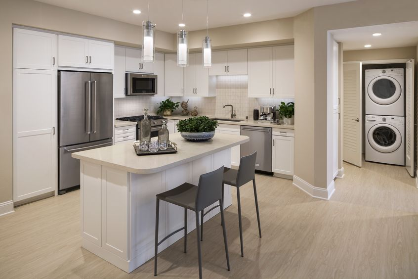 Interior view of kitchen and laundry unit at Villas Fashion Island Apartment Homes in Newport Beach, CA.