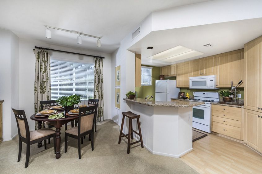 Interior view of dining room and kitchen at Rancho Monterey Apartment Homes in Tustin, CA.