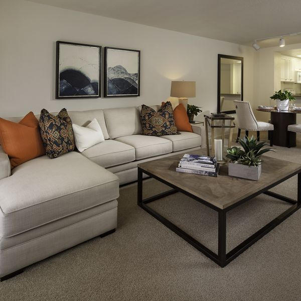 Interior view of living room, dining, and kitchen at Rancho Tierra Apartment Homes in Tustin, CA.