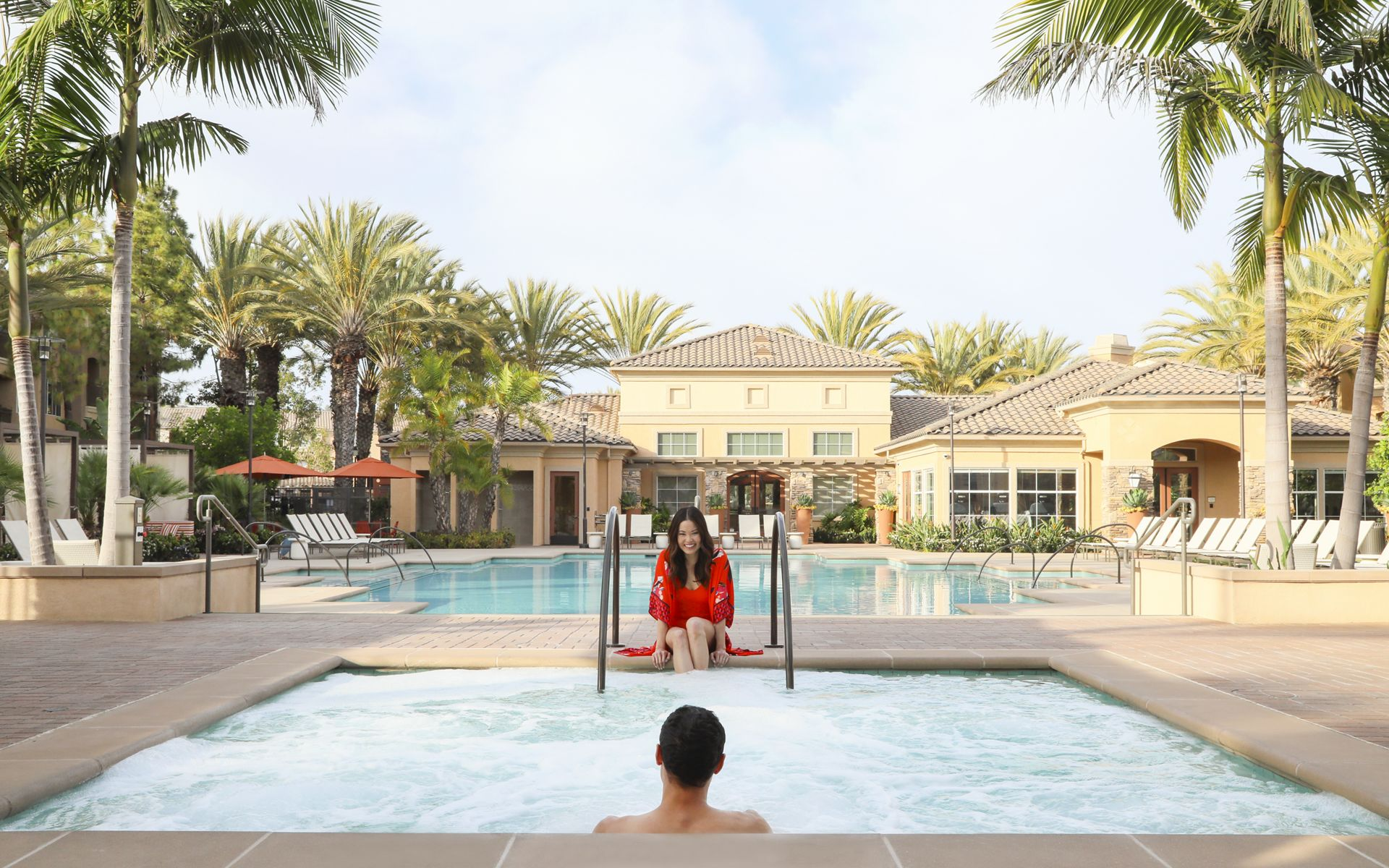 People spending time in the pool and spa at Del Rio Apartment Homes in Mission Valley, CA.