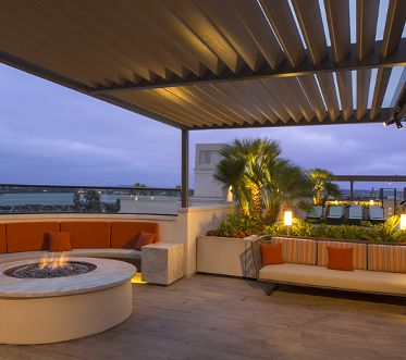 Exterior view of roof deck lounge area and fireplace at Harborview Apartment Homes in San Diego, CA.
