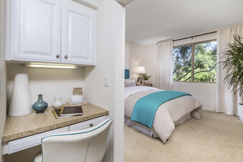 Interior view of bedroom and work from home desk area at Pacific View Apartment Homes in Carlsbad, CA.