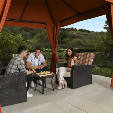 View of people spending time at the outdoor lounge at Pacific View Apartment Homes in Carlsbad, CA.