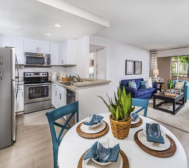 Interior view of dining room, kitchen and living room at Solazzo Apartment Homes in La Jolla, CA.