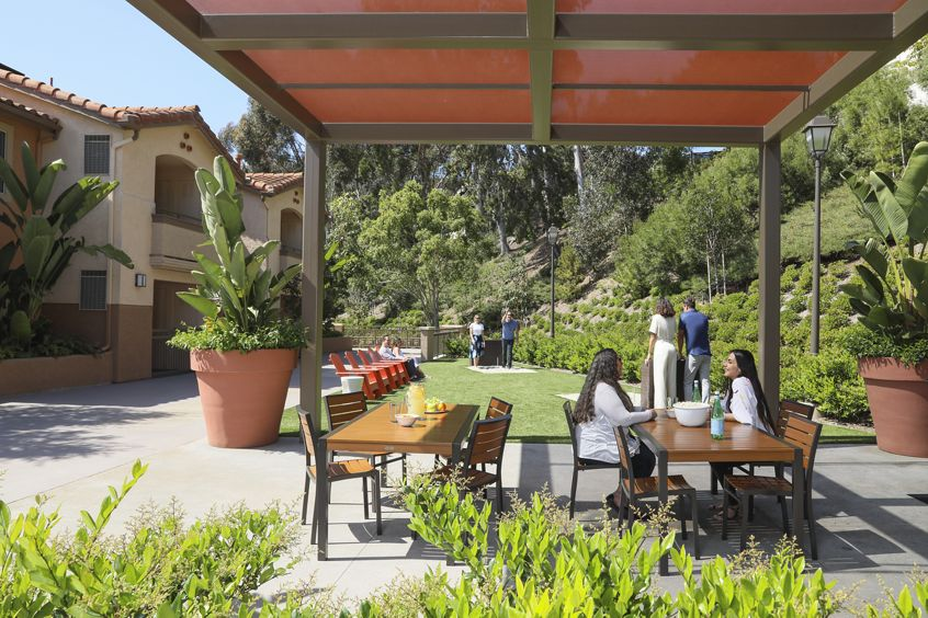 People eating at the outdoor patio area at Solazzo Apartment Homes in San Diego.