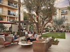 Exterior view of people spending time in lounge courtyard at The Villas of Renaissance Apartment Homes in San Diego, CA.