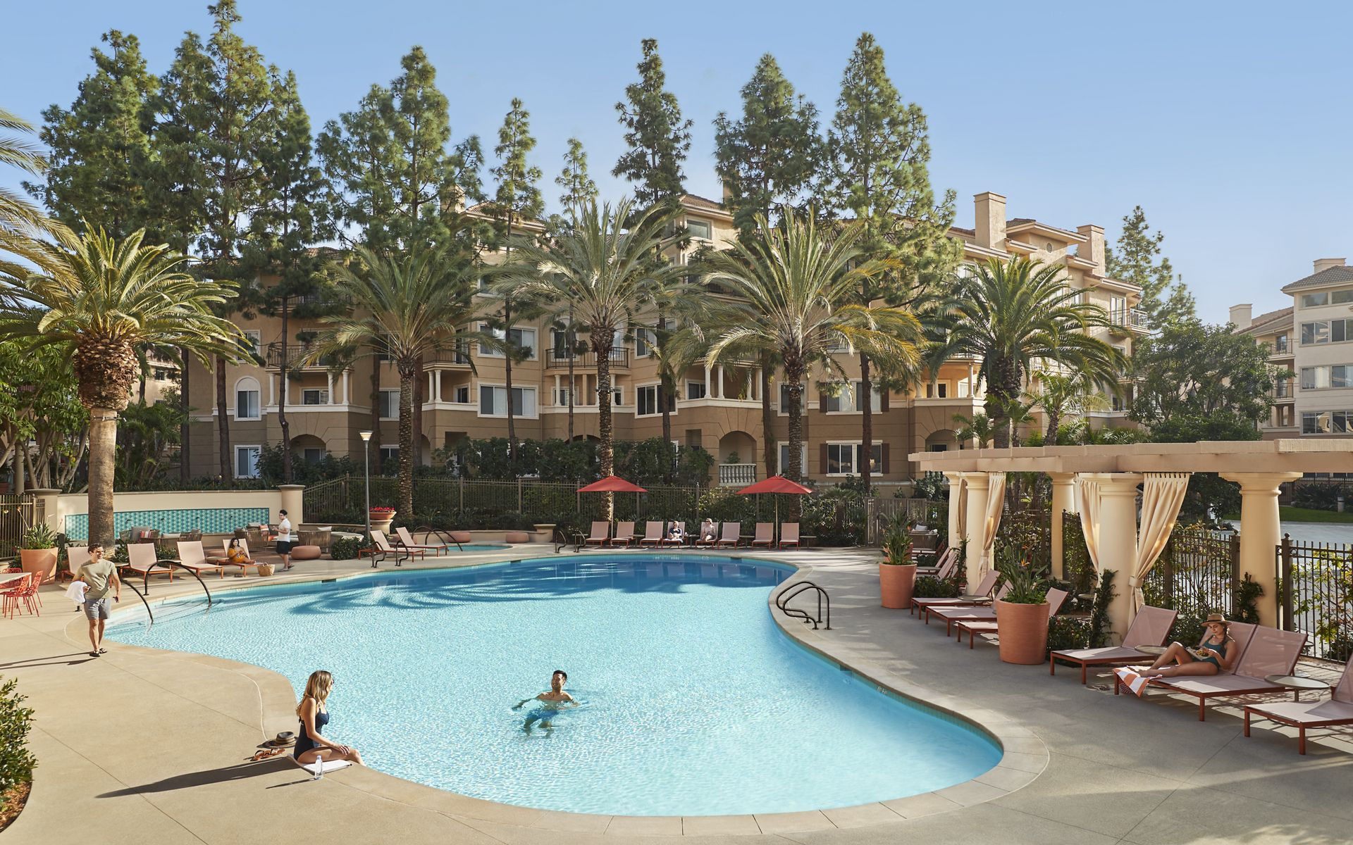 People spending time by pool at The Villas of Renaissance Apartment Homes in San Diego, CA.