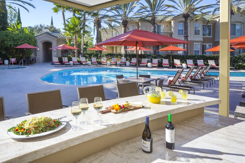 Exterior view of pool and BBQ area at Torrey Villas Apartment Homes in San Diego, CA.