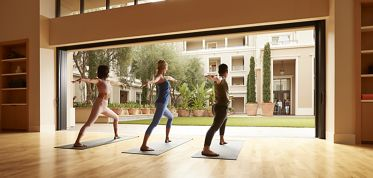 Interior view of residents doing yoga at yoga fitness center at Irvine Company Apartment Communities.