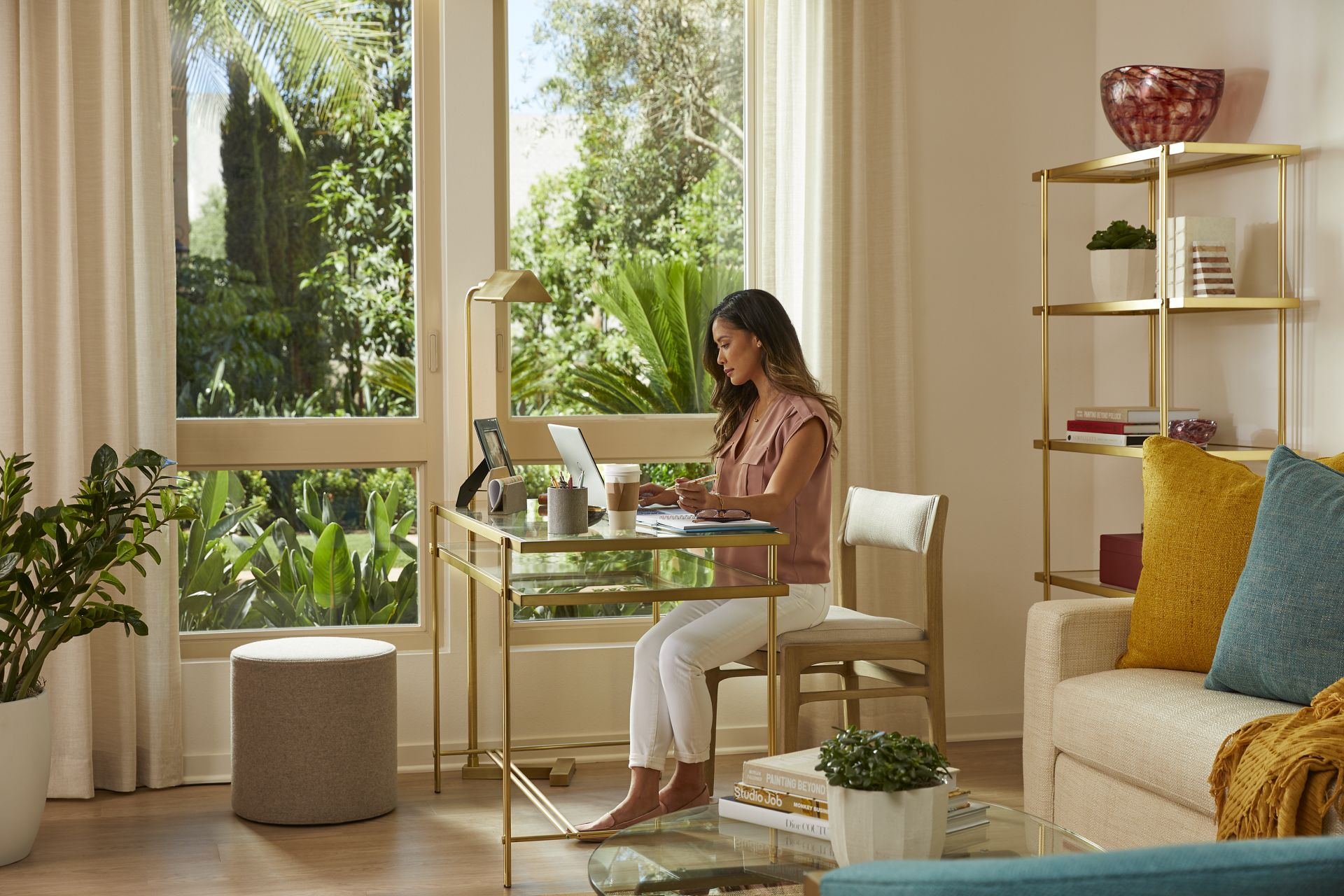 Interior view of woman working from home at Promenade Apartment Homes in Irvine, CA.