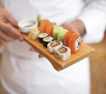 sushi chef holding sushi plate.(shallow depth of field)