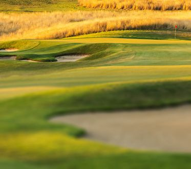Golf Coarse at sunset with bunker, green and pin in view