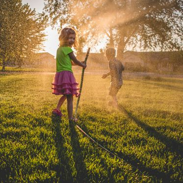Little girl sprays her brother with a garden hose.