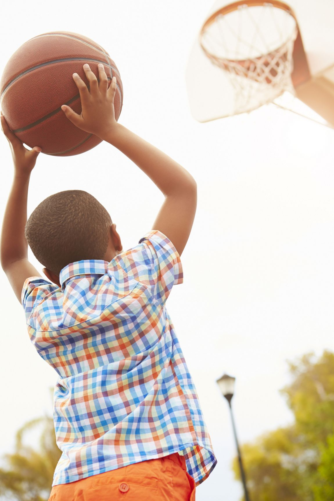 Rear View Of Boy On Basketball Court Shooting For Basket Hoding