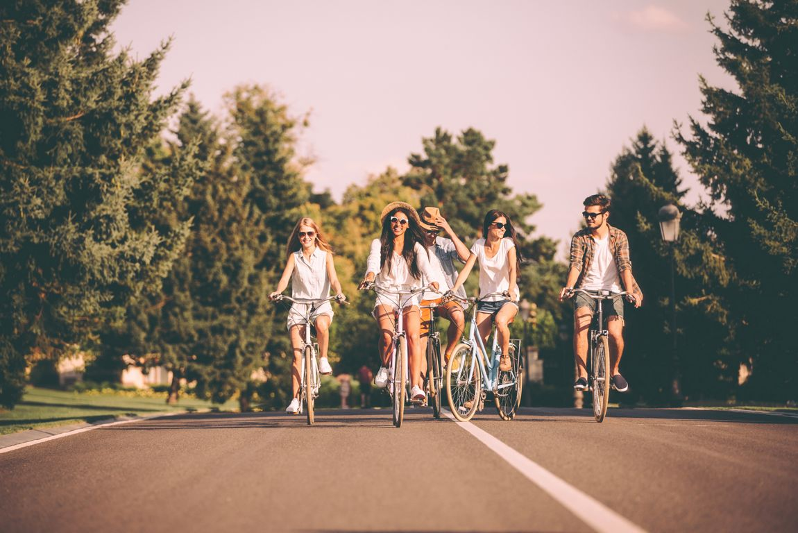 Group of young people riding bicycles along a road and looking happy