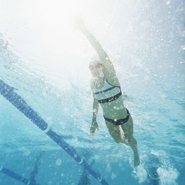 Low Angle Shot of a Young Woman Swimming in a Pool