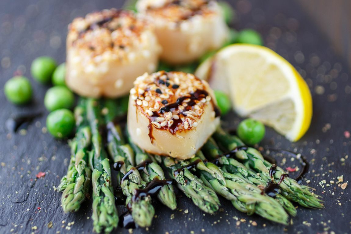 Fried scallop  with sesame seeds and balsamic sauce, asparagus, lemon and green peas on a black plate. Shallow depth of field